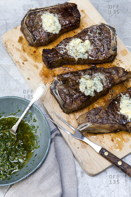 Grilled strip steaks with blue cheese butter and salsa verde