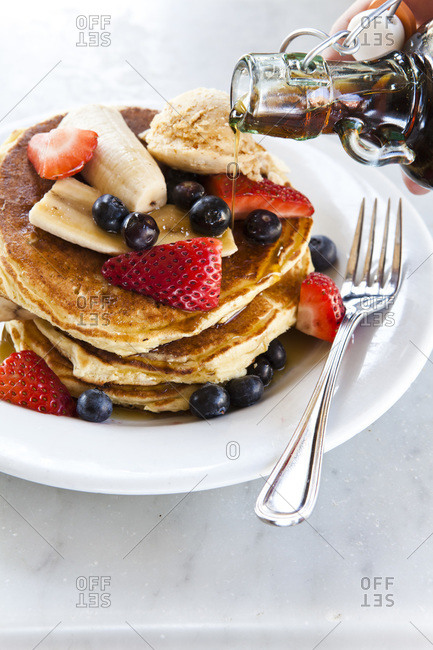 Stack of pancakes with fresh fruits and maple syrup