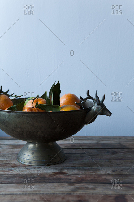 Orange in rustic copper bowl with deers
