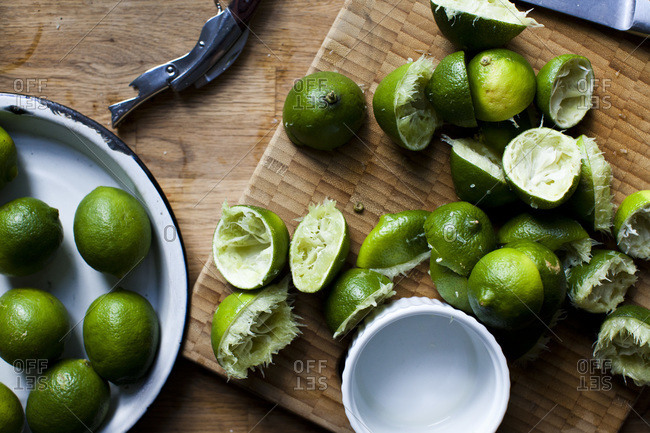 Overhead view of whole and halved limes on wooden cutting board