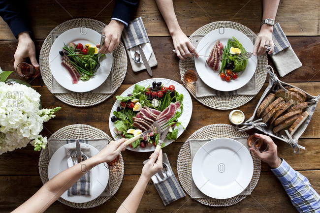 Overhead view of friends eating medium rare tuna and green salad