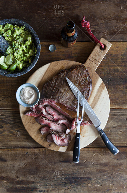 Sliced medium rare beef on cutting board with guacamole