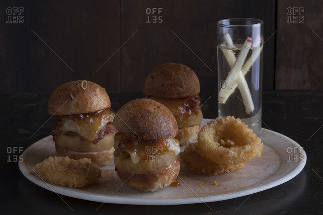 Grilled mulled apple and ham sliders with apple butter top with a crisp apple ring dusted with hickory nuts