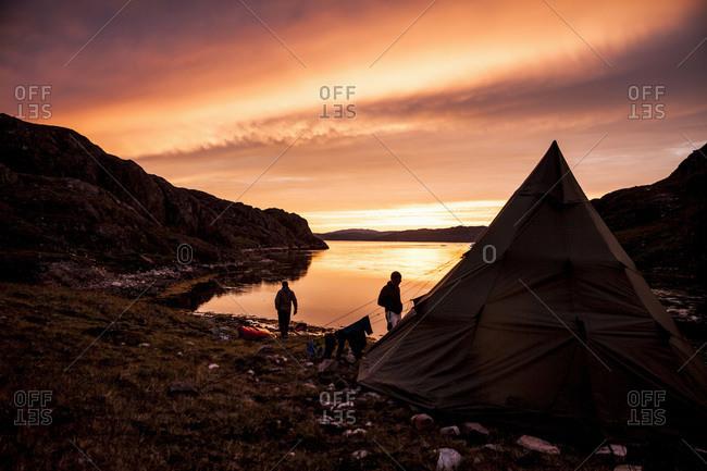 People camping near lake at dusk