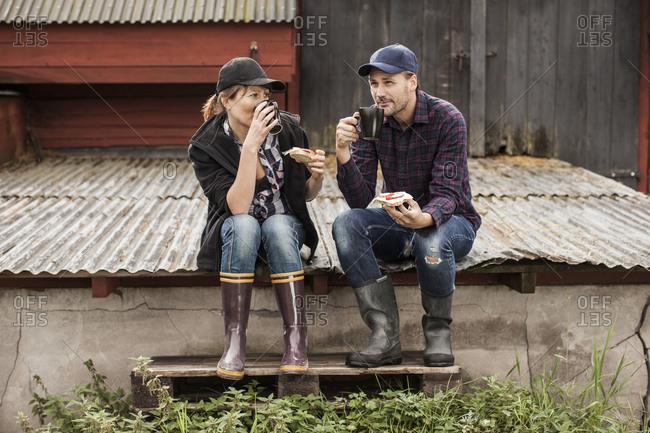 Full length of couple having breakfast on corrugated iron at farm