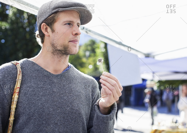 Thoughtful man eating with toothpick at market