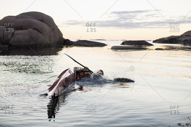 Man falling into water while kayaking