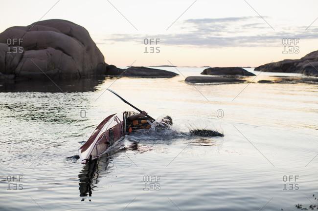 Man falling into water while kayaking