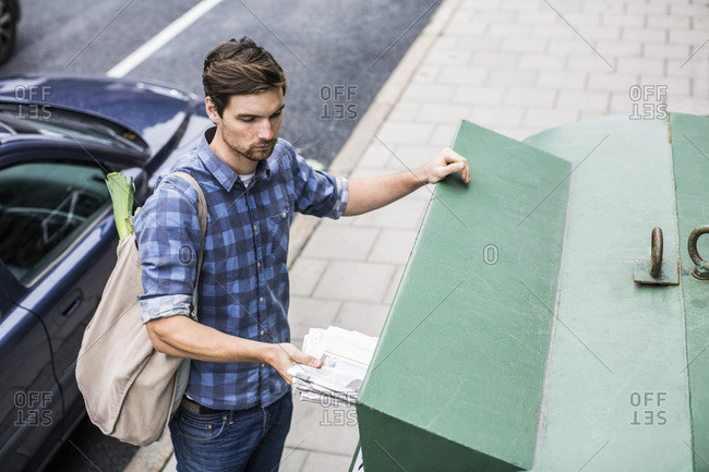 Young man putting newspaper in recycling bin
