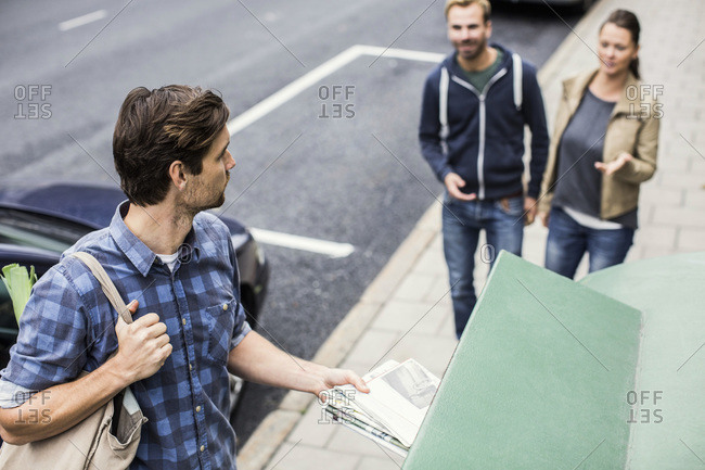 Man putting newspaper in recycling bin while looking at friends on sidewalk