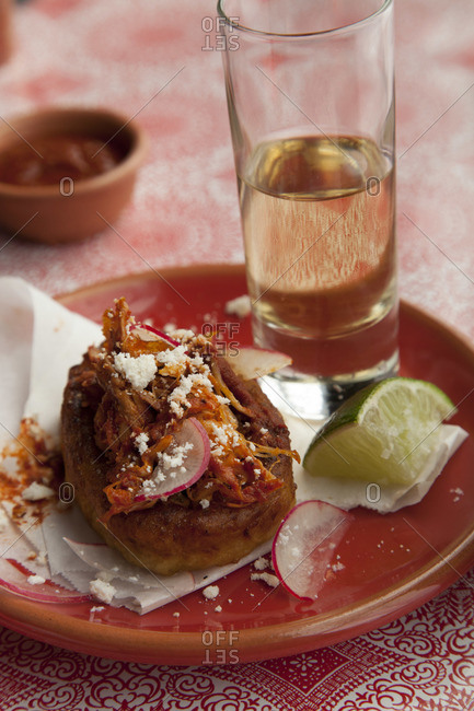 Close-up of garnachas de tinga de conejo with lime wedge and mezcal