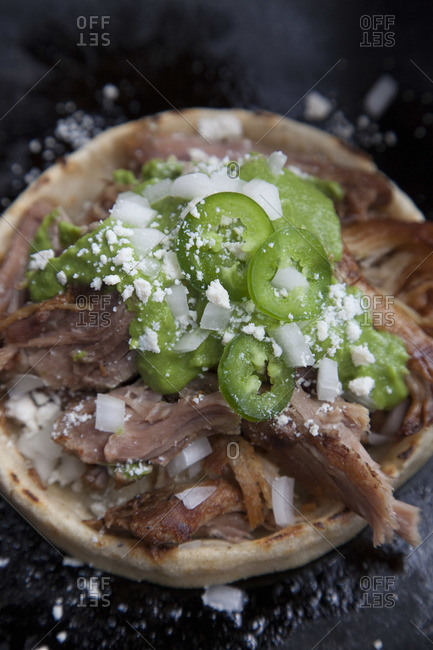Close up of Mexican sopes with beef, jalapeno and chopped onion