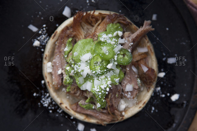 Top view of Mexican sopes with beef, jalapeno and chopped onion