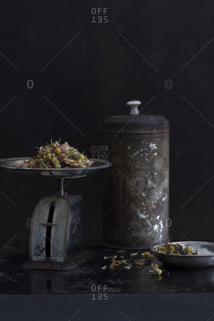 Still life of rusty scale, container and heap of dried herbal tea