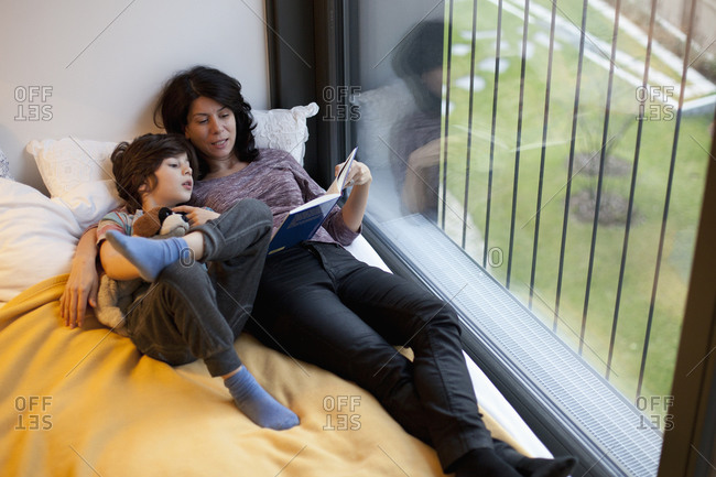 Woman reading a bedtime story for a boy