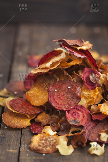Roasted vegetable chips made of parsnips, sweet potatoes, beetroots, carrots and turnips on wooden table