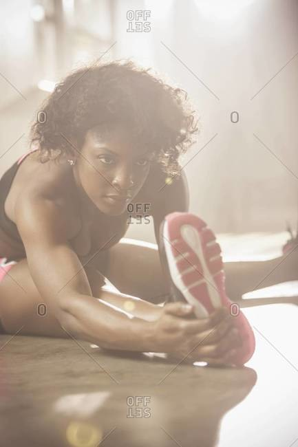 Black woman stretching in gym