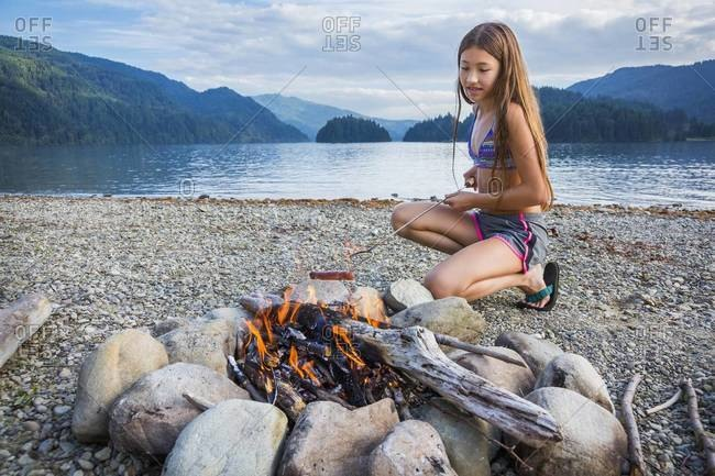 Young girl roasting a hot dog at campfire