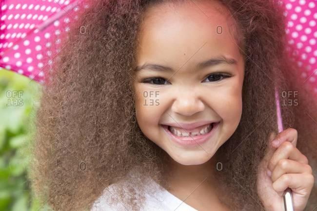 Mixed race girl smiling under umbrella