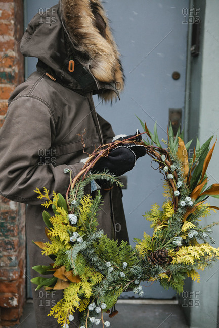 A unidentifiable person holding a festive wreath outdoors