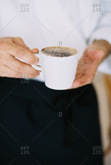 A person holding a cup of frothy coffee