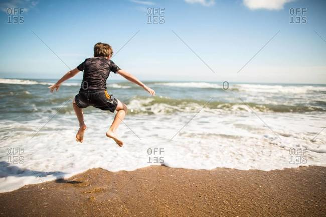 A boy jumping to avoid the surf