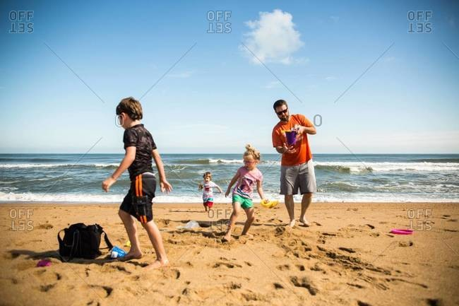 A father helping his children build a sandcastle