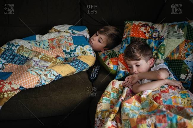 Two boys lying down on a couch