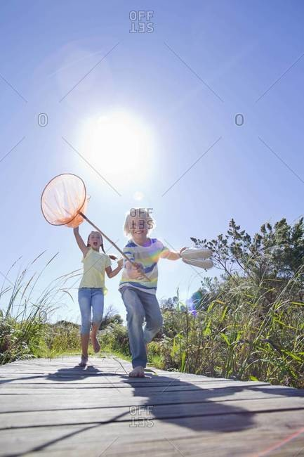 Enthusiastic boy and girl running barefoot with fishing nets
