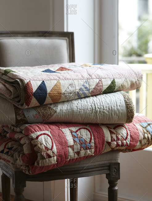 Quilts stacked on chair