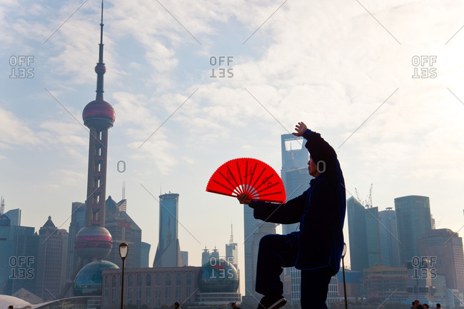 Practicing Tai Chi with fan, and Pudong skyline, early morning, Shanghai, China