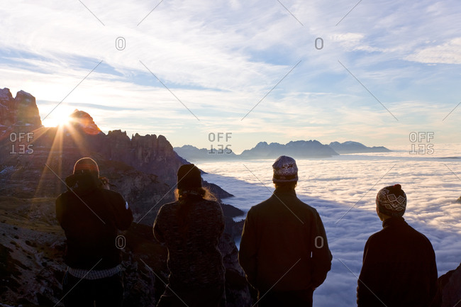 Group of young men watching sunrise above cloud line, Hochpustertal-Dolomiti di Sesto Natural Park, Italy