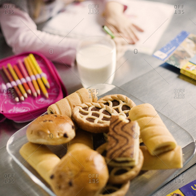 Girl studying at table with snack and milk