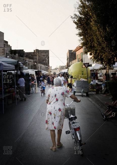 Rear view of senior woman leaning on bicycle and walking to market