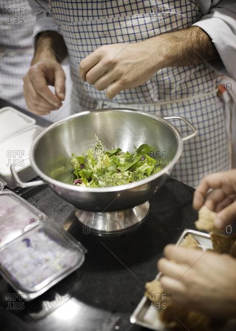Man preparing salad in kitchen