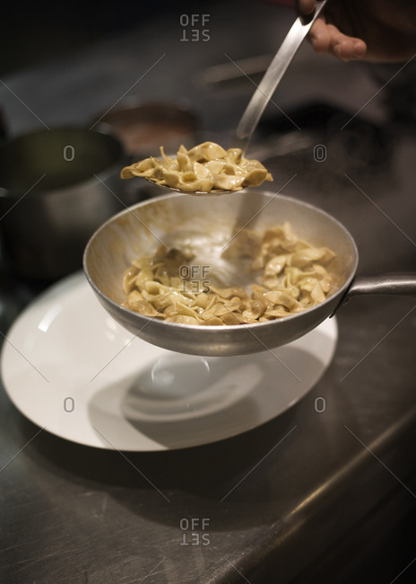 Traditional Italian tortellini with butter being served on a plate