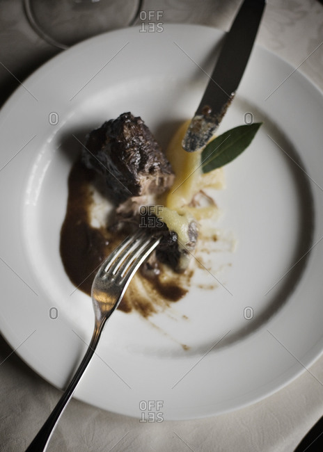 Overhead view of beef with brown sauce and smashed potato