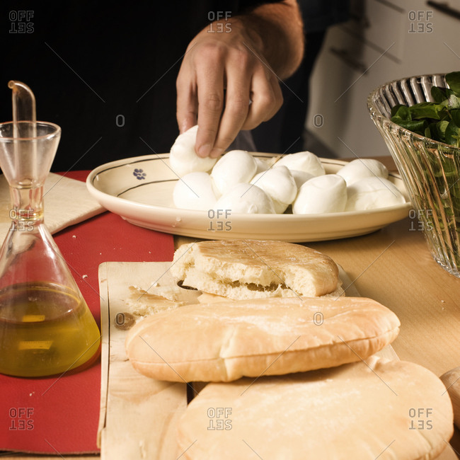 Man eating mozzarella in kitchen