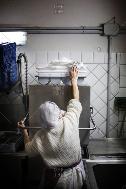 Woman reaching for a kitchen towel in an industrial kitchen