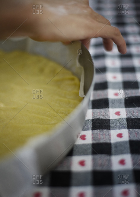 Baker adjusting parchment paper under the pastry
