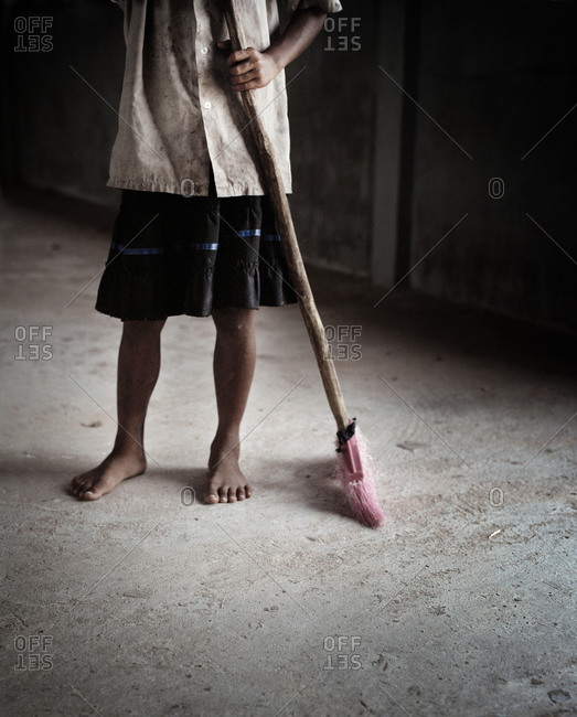 Low angle view of worker standing with broom.