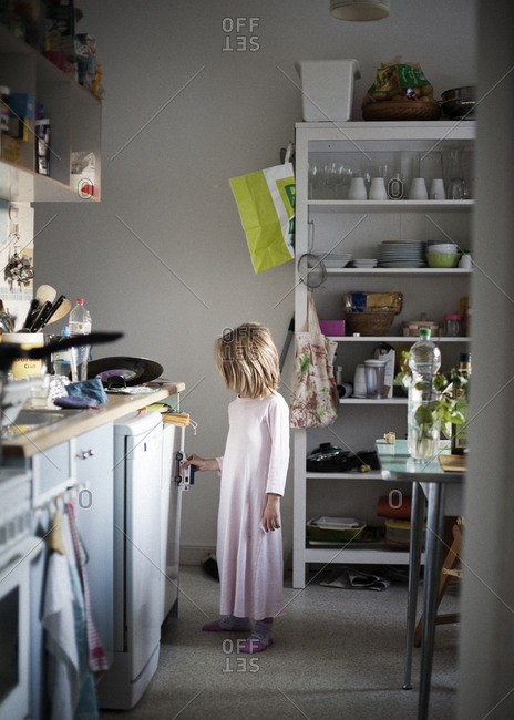 Young girl in pink nightgown playing in kitchen
