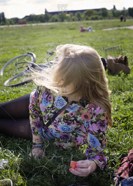 Blond teenage girl resting on grass and eating strawberry