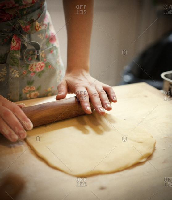 Woman rolling out pasta dough thinly