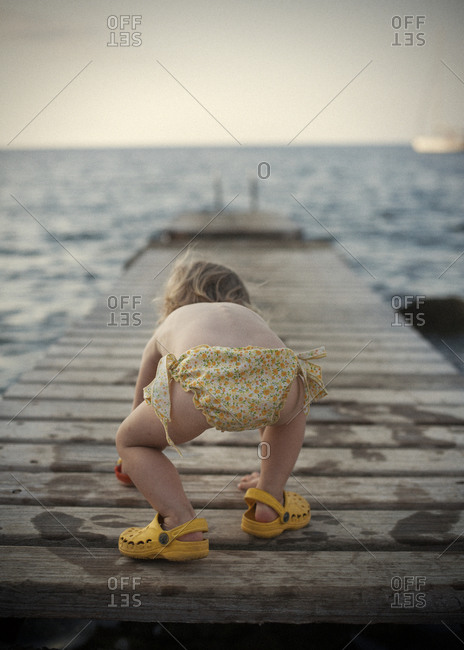 Rear view of toddler girl playing on jetty
