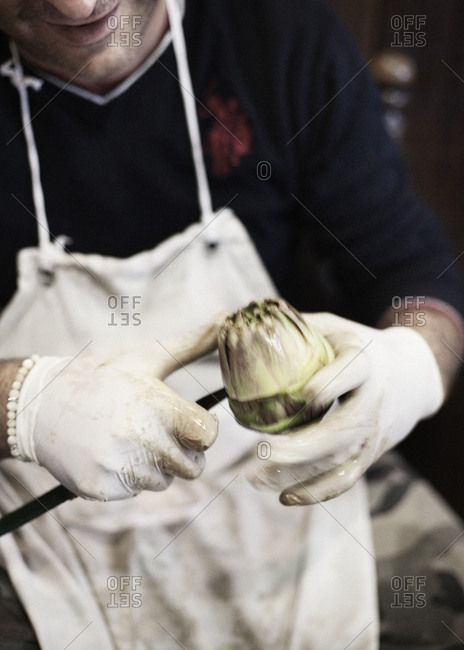 Mid section view of man cutting an artichoke