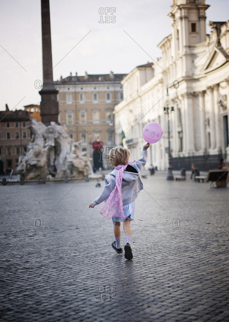 Young girl running with pink balloon toward the fountain in Piazza Navona, Rome