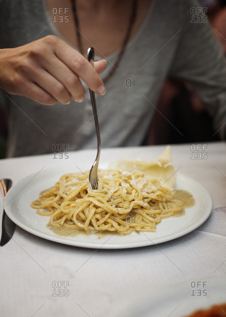 Woman eating pasta dish