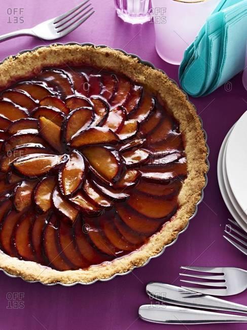Whole plum tart served on table