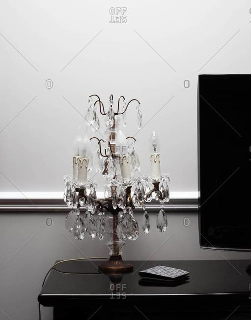Crystal chandelier table lamp next to TV set